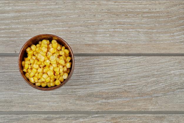 Uma tigela de milho doce cozido em uma mesa de madeira.