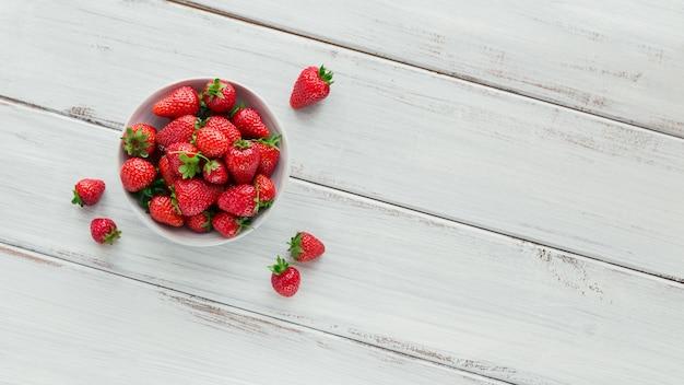 Uma tigela de morangos suculentos vermelhos na mesa de madeira branca. conceito de lanches saudáveis e dieta.