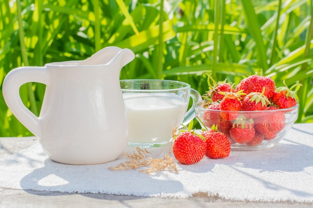 Uma tigela de morangos, um copo com leite e um jarro em um guardanapo em uma mesa de madeira