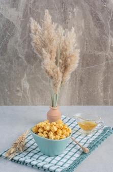 Uma tigela de pipoca de caramelo, um copo de mel, uma colher de mel e talos de grãos em um vaso de cerâmica e na toalha sobre superfície de mármore