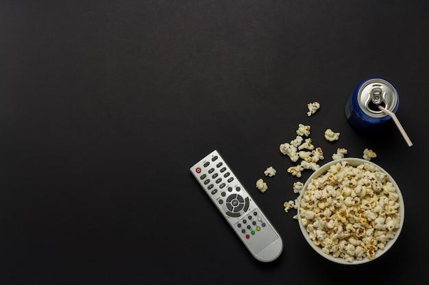 Uma tigela de pipoca, um controle remoto de tv, uma lata de bebida em um fundo preto. o conceito de assistir tv, filmes, séries de tv, esportes, shows. vista plana leiga, superior.