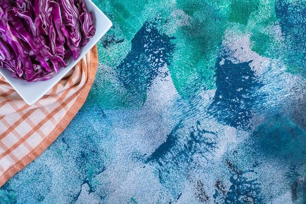 Uma tigela de repolho roxo fresco em um pano de prato