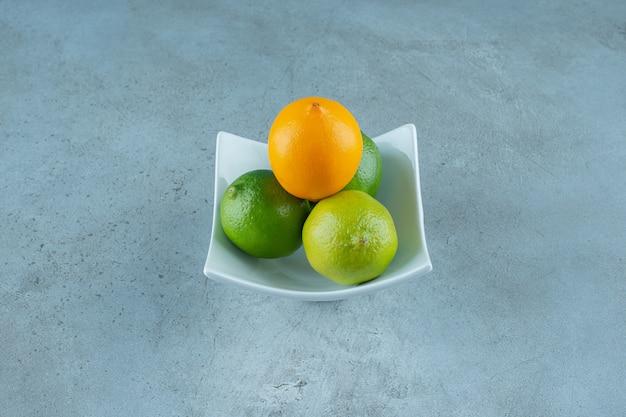 Uma tigela de saborosos limões, na mesa de mármore.