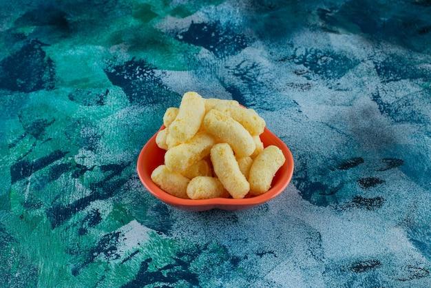 Uma tigela de saborosos palitos de milho, na mesa azul.