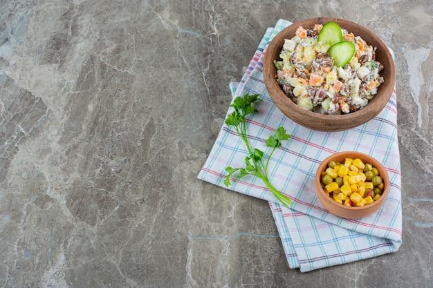 Uma tigela de salada de legumes ao lado de uma salada de milho em uma tigela sobre um pano de prato, no fundo de mármore.