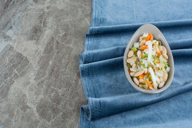 Uma tigela de salada de legumes em pedaços de tecido no mármore.