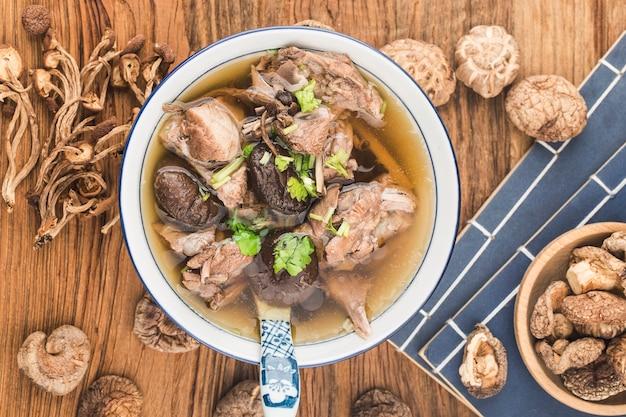 Uma tigela de sopa de cogumelos e pato lao em uma tábua
