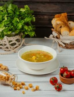Uma tigela de sopa de galinha com batata, cenoura e endro, servida com fatias de pão
