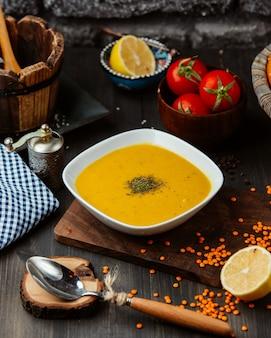 Uma tigela de sopa de lentilha na mesa de madeira preta