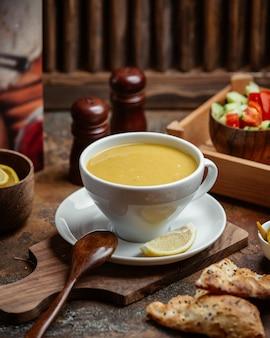 Uma tigela de sopa de lentilha servida com limão