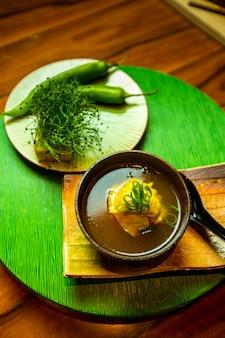 Uma tigela de sopa japonesa e um prato de pimenta verde e ervas