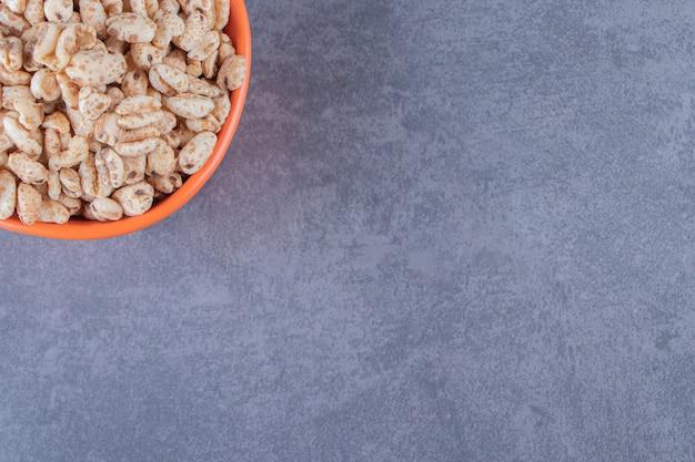 Uma tigela de sucrilhos secos, sobre o fundo azul.