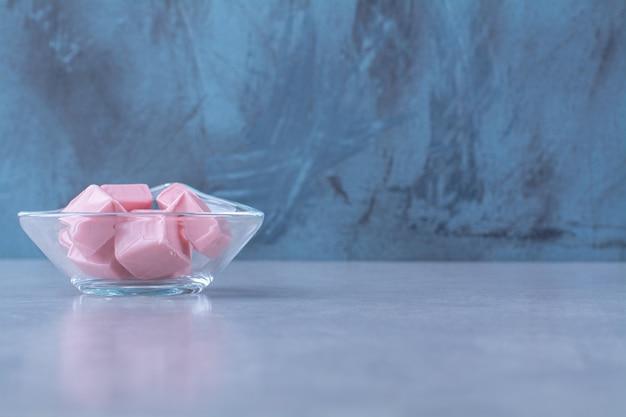 Uma tigela de vidro cheia de confeitaria doce rosa pastila