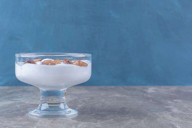 Uma tigela de vidro cheia de iogurte saudável com deliciosos cereais.