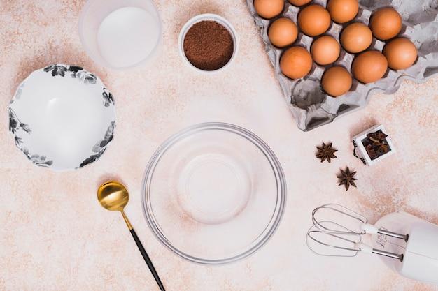 Uma tigela de vidro vazia; placa; farinha; cacau em pó; caixa de ovos; anis estrelado e batedeira no balcão da cozinha