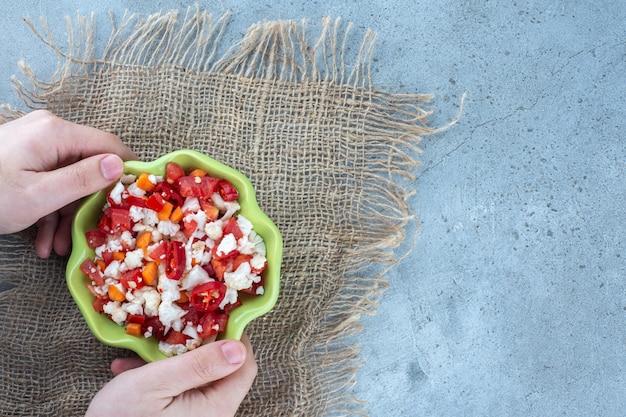 Uma tigela pequena de salada de couve-flor e pimenta segurada com as mãos sobre uma superfície de mármore