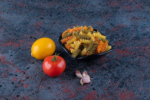 Uma tigela preta cheia de macarrão multicolorido com tomate vermelho fresco e limão em uma superfície escura.