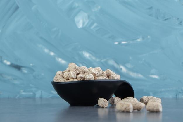 Uma tigela preta de cereais crocantes de centeio.