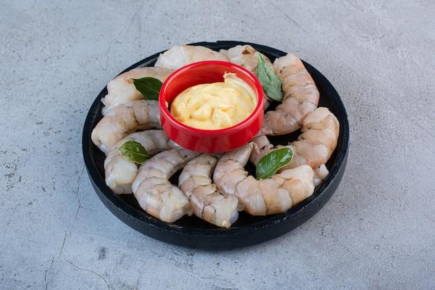 Uma tigela preta de deliciosos camarões com mostarda em um fundo de pedra.