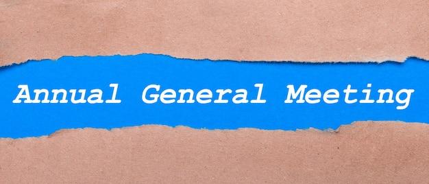 Uma tira de papel azul com a inscrição assembleia geral anual entre o papel pardo. vista de cima