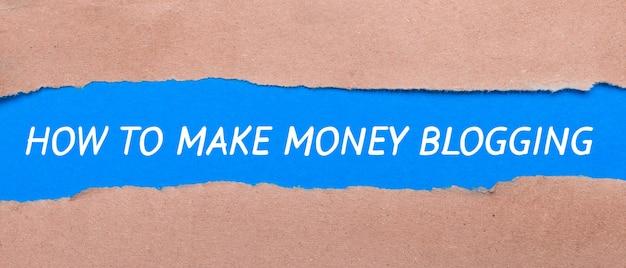Uma tira de papel azul com as palavras blogging como fazer dinheiro entre o papel pardo. vista de cima
