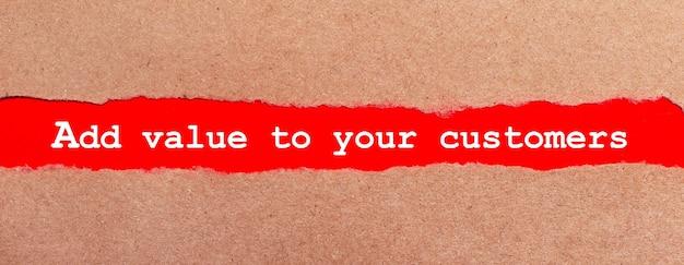 Uma tira de papel vermelho sob o papel marrom rasgado. letras brancas em papel vermelho agregam valor aos seus clientes. vista de cima
