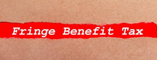 Uma tira de papel vermelho sob o papel marrom rasgado. letras brancas em papel vermelho imposto de benefícios fringe. vista de cima