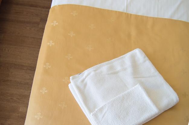Uma toalha branca sobre uma luxuosa colcha dourada na cama, uma visão de cima de perto.