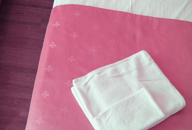 Uma toalha branca sobre uma luxuosa colcha rosa na cama, uma visão de cima de perto.