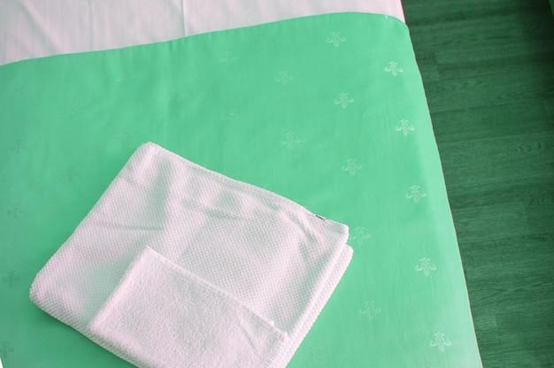 Uma toalha branca sobre uma luxuosa colcha verde na cama, uma visão de cima de perto.