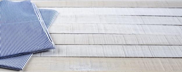 Uma toalha de chá de listras azuis e brancas sobre fundo branco de madeira rústica