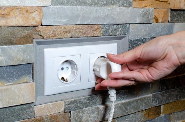 Uma tomada com ficha elétrica na parede. conceito de economia de energia.