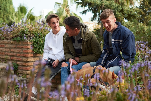 Uma tomada de foco superficial de três jovens sentados em um jardim cuidando de um faraó hound