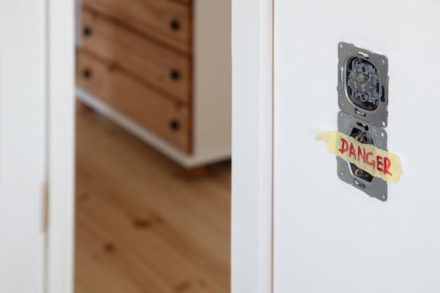 Uma tomada e comutador das luzes instaladas na parede branca
