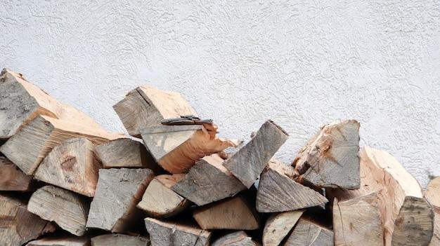 Uma tora de madeira cortada cuidadosamente dobrada. o fogo está derretendo. lenha empilhada uma em cima da outra. a lenha é recolhida para aquecimento no tempo frio. textura de fundo de lenha seca empilhada.