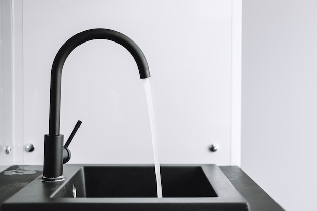 Uma torneira com a água correndo na cozinha
