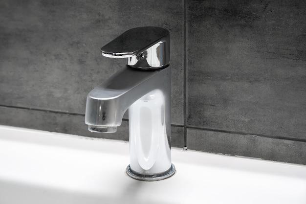 Uma torneira de metal cromado embaçada para água quente e fria, localizada em uma pia branca contra uma parede de concreto cinza em um banheiro moderno. foco seletivo. copie o espaço