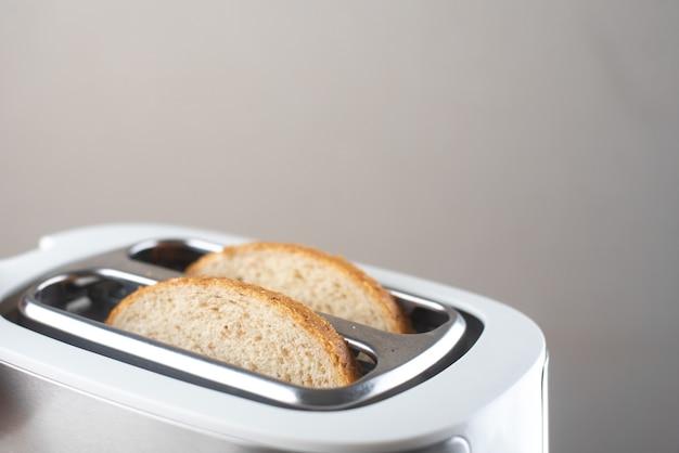 Uma torradeira branca e prata em uma parede cinza em uma mesa de madeira branca com pedaços de pão para fora