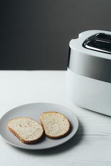 Uma torradeira branca e prata está em uma mesa de madeira branca com fatias de pão ao lado