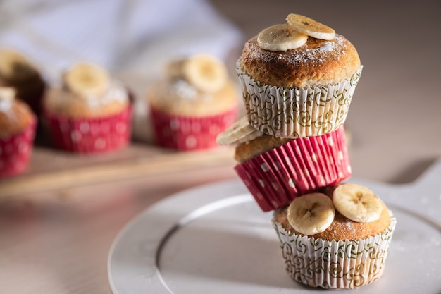 Uma torre de três muffins de banana caseiros de perto, foco seletivo, conceito de cozimento caseiro fácil, horizontal