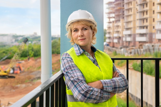 Uma trabalhadora da construção civil usando colete e capacete no fundo de um novo prédio