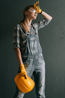 Uma trabalhadora de capacete está cansada e enxuga o suor da testa