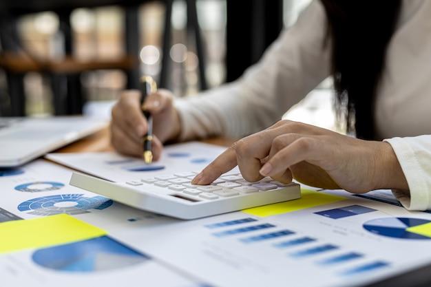 Uma trabalhadora financeira pressiona uma calculadora para verificar a exatidão das informações nos documentos financeiros da empresa, ela prepara o resumo financeiro da empresa para uma reunião com a gerência.
