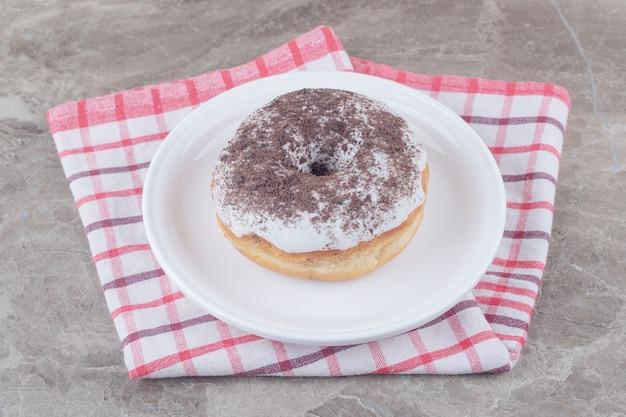 Uma travessa com um donut em uma toalha sobre mármore