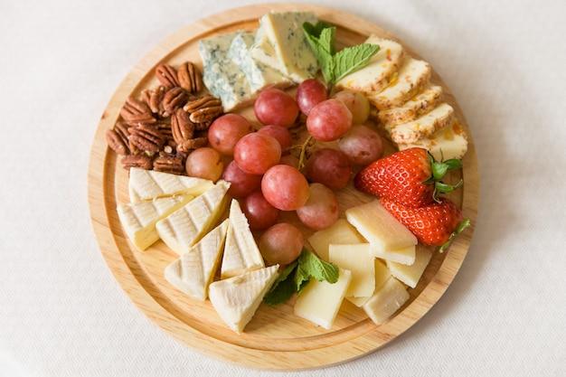 Uma travessa de madeira com deliciosos queijos servidos com uvas orgânicas, nozes, morangos e hortelã