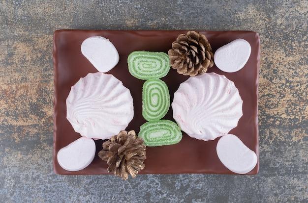 Uma travessa de marshmallows, marmeladas, biscoitos e pinhas na superfície de madeira
