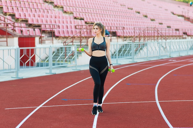 Uma treinadora de cabelo escuro está na pista de corrida vermelha do estádio, vestida com um uniforme esportivo.