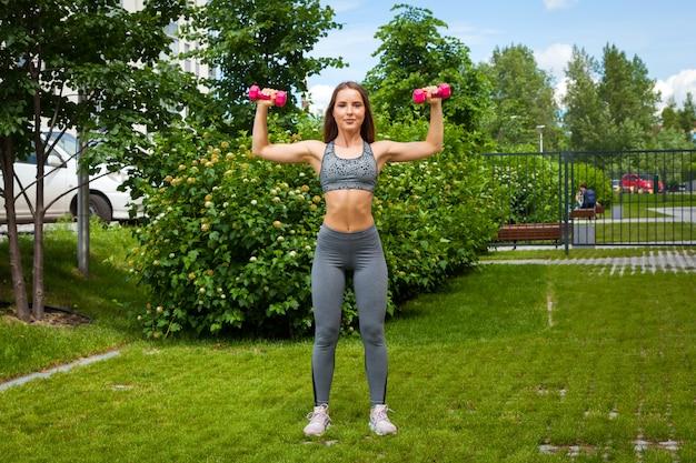Uma treinadora de cabelos escuros com uma blusa curta esportiva e leggings de ginástica faz um balanço à mão nos lados com halteres em um dia de verão em um parque em um gramado verde