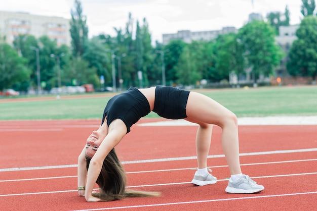 Uma treinadora de cabelos escuros está na pista de corrida vermelha do estádio, vestida com uniforme esportivo. Foto Premium