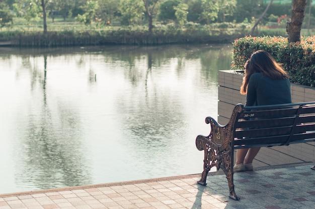 Uma triste, chateada e preocupada mulher sentada sozinha ao ar livre